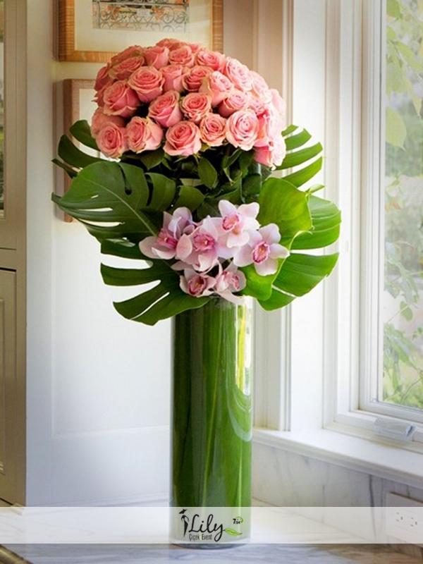 silindir vazoda pembe güller ve orkideler